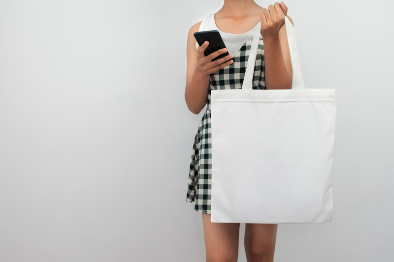 young woman holding eco cotton bag and using mobile isolate on w